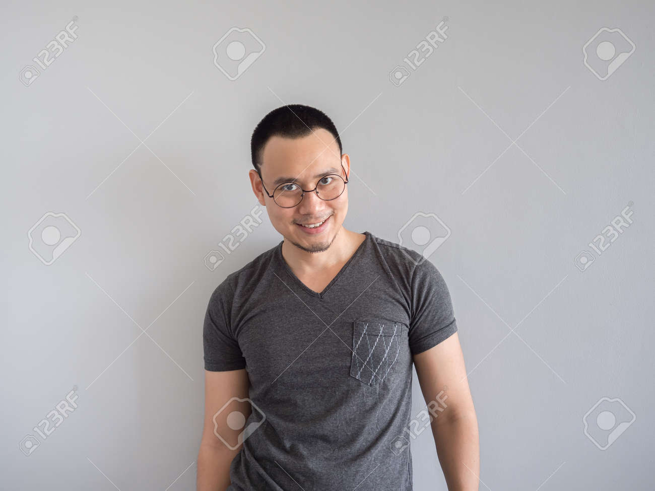 Happy Asian Freelance Man With Skinhead And Relaxing Mile Haircut