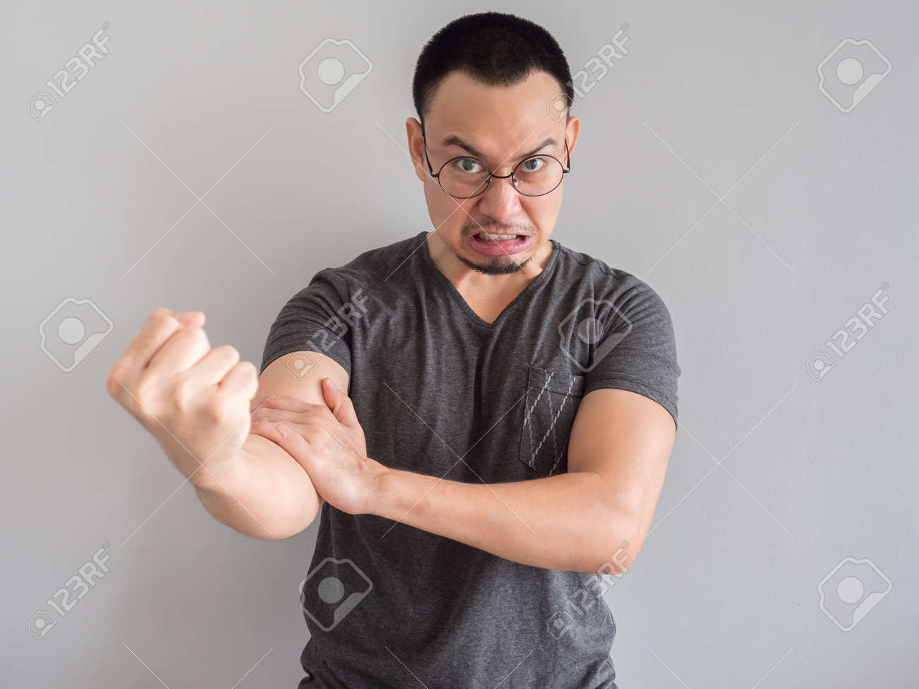 angry and crazy asian man in black t-shirt and skinhead hair..