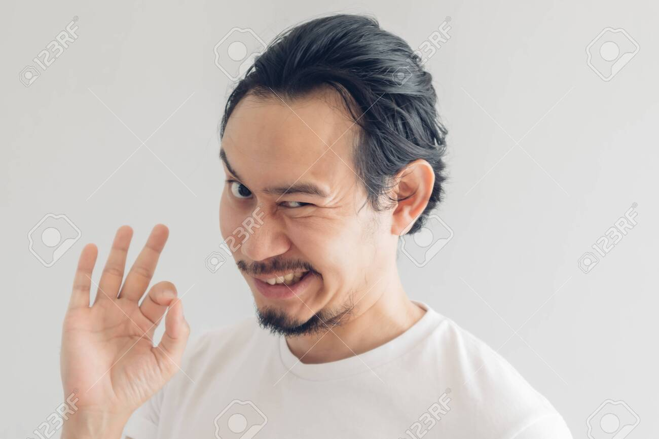 Funny grinning smile face of Asian man in white t-shirt and grey background. - 153588593