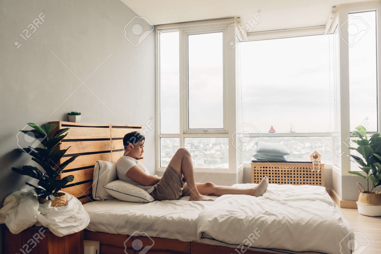 Lonely and depressed Asian man in his bedroom in the apartment. - 155188836