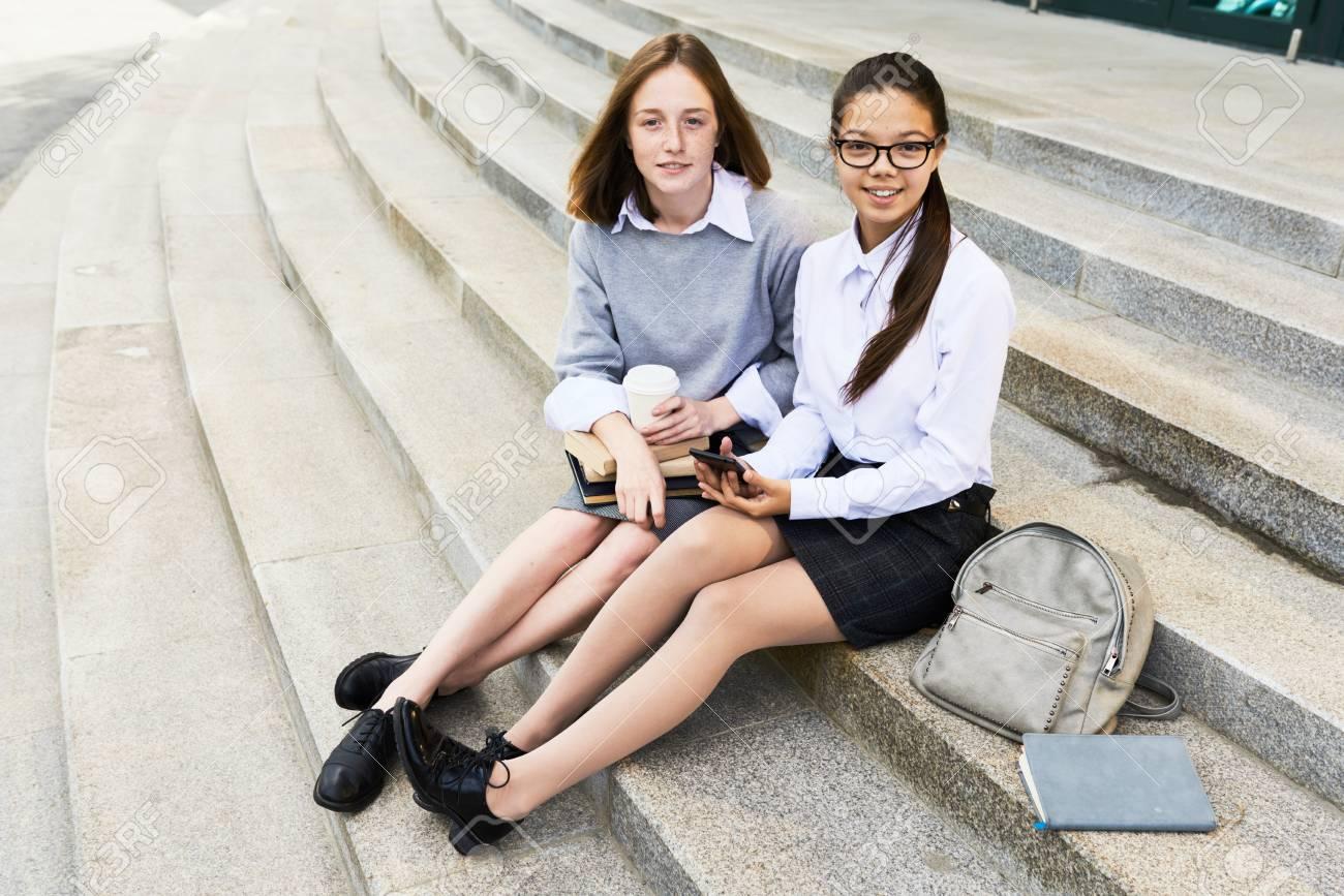 3206ac1c2 Retrato de dos colegialas bonitas que miran la cámara mientras que se  sienta en las escaleras de piedra al aire libre