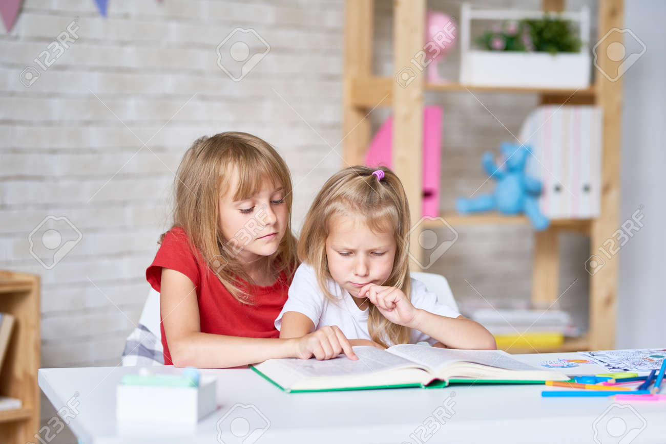 Adorable little sisters wrapped up in reading adventure story while sitting at table in their cozy bedroom - 83829592