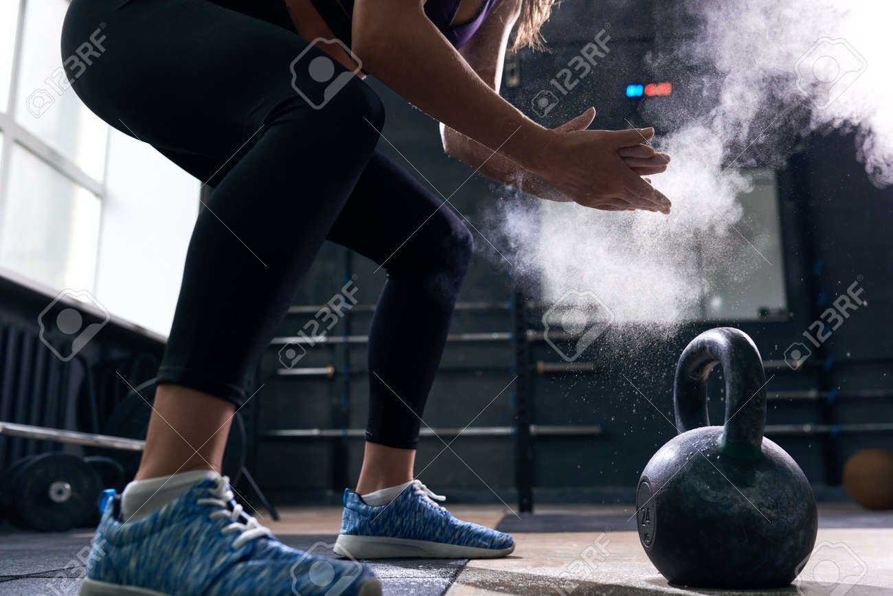 Side view closeup of unrecognizable young woman rubbing her hands with talk puffing cloud preparing to lift kettlebells during crossfit workout in modern gym - 83831207