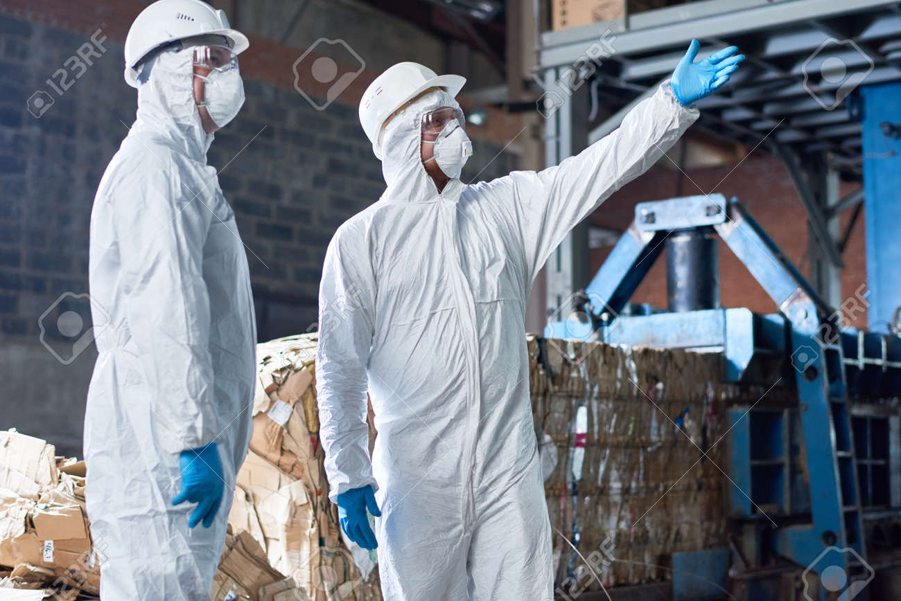 Workers in Hazmat Suits at Modern Factory - 91469893