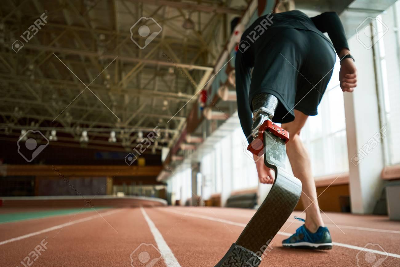 Imagem Motivacional Do Atleta Jovem Amputado Na Posição Inicial Na Pista De Corrida No Estádio Indoor Moderno Foco No Pé Artificial Cópia Espaço
