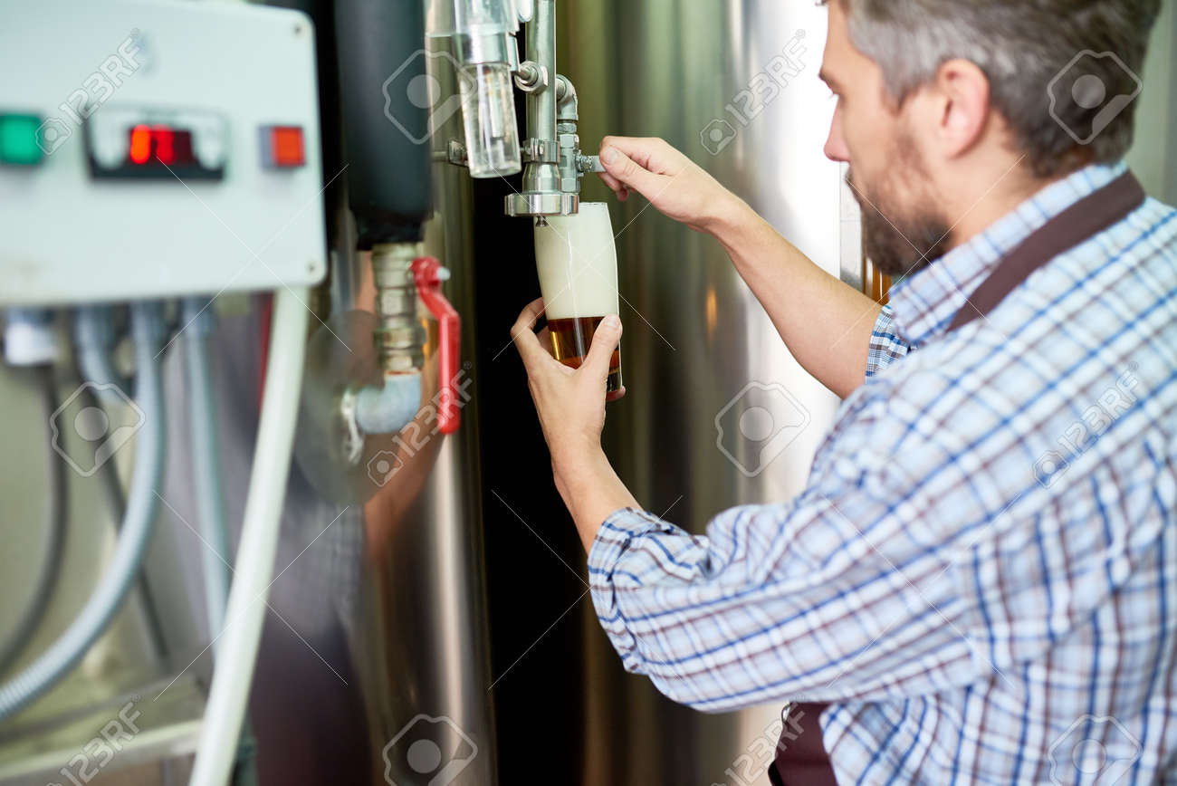 Fantastisch Modern Brewer Pouring Fresh Beer Into Glass At Plant Stock Photo   95561225