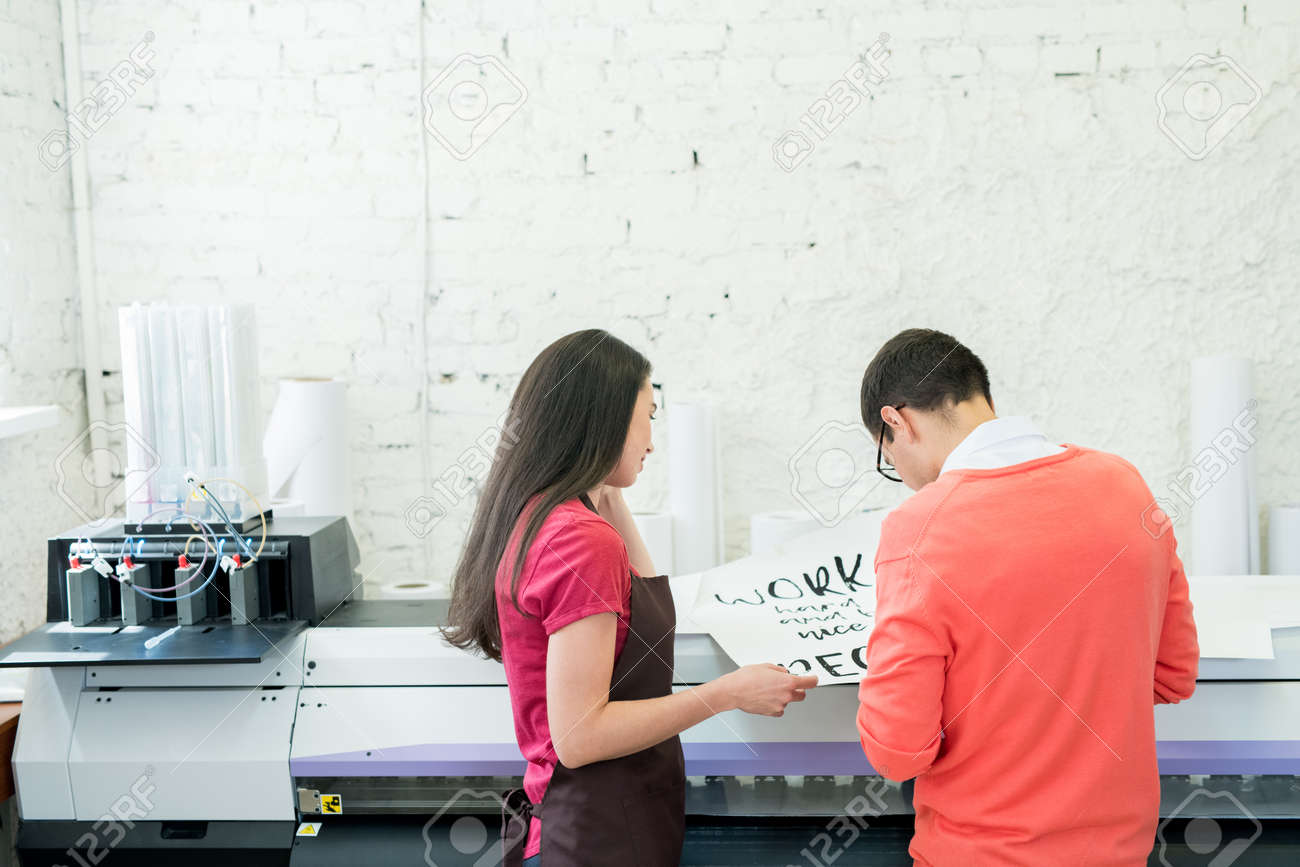 Printing specialists examining banner in office - 108969831