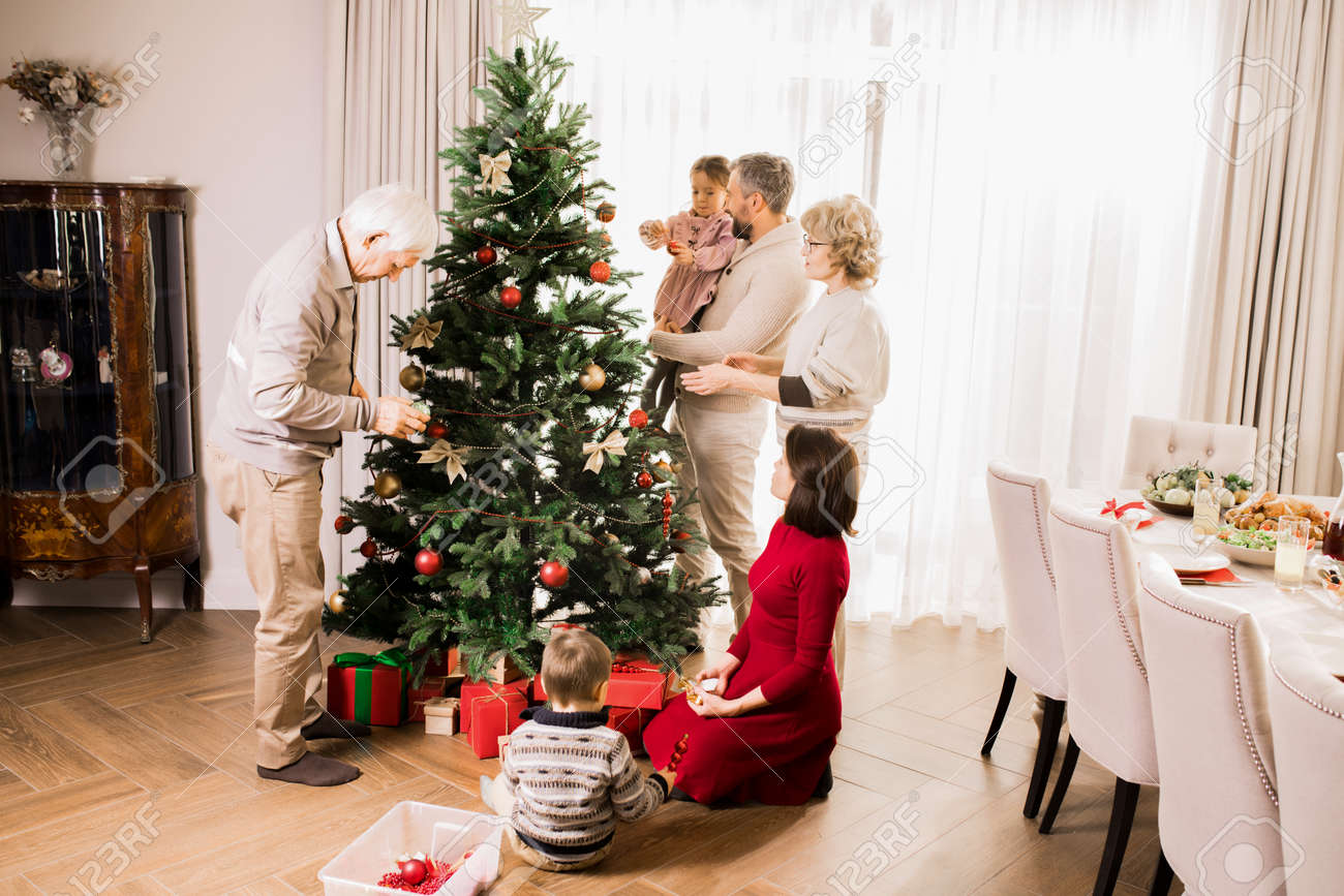 Big Family Decorating Christmas Tree at Home - 113892462