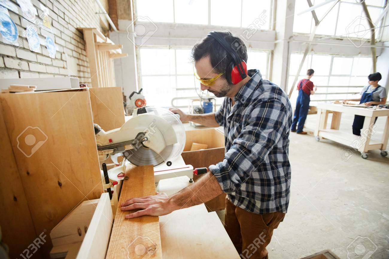 Concentrated man cutting wooden piece - 116766828