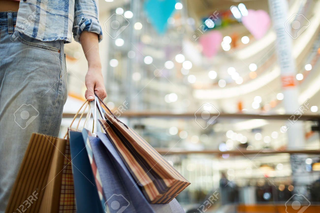 Carrying shopping bags in mall - 119630703
