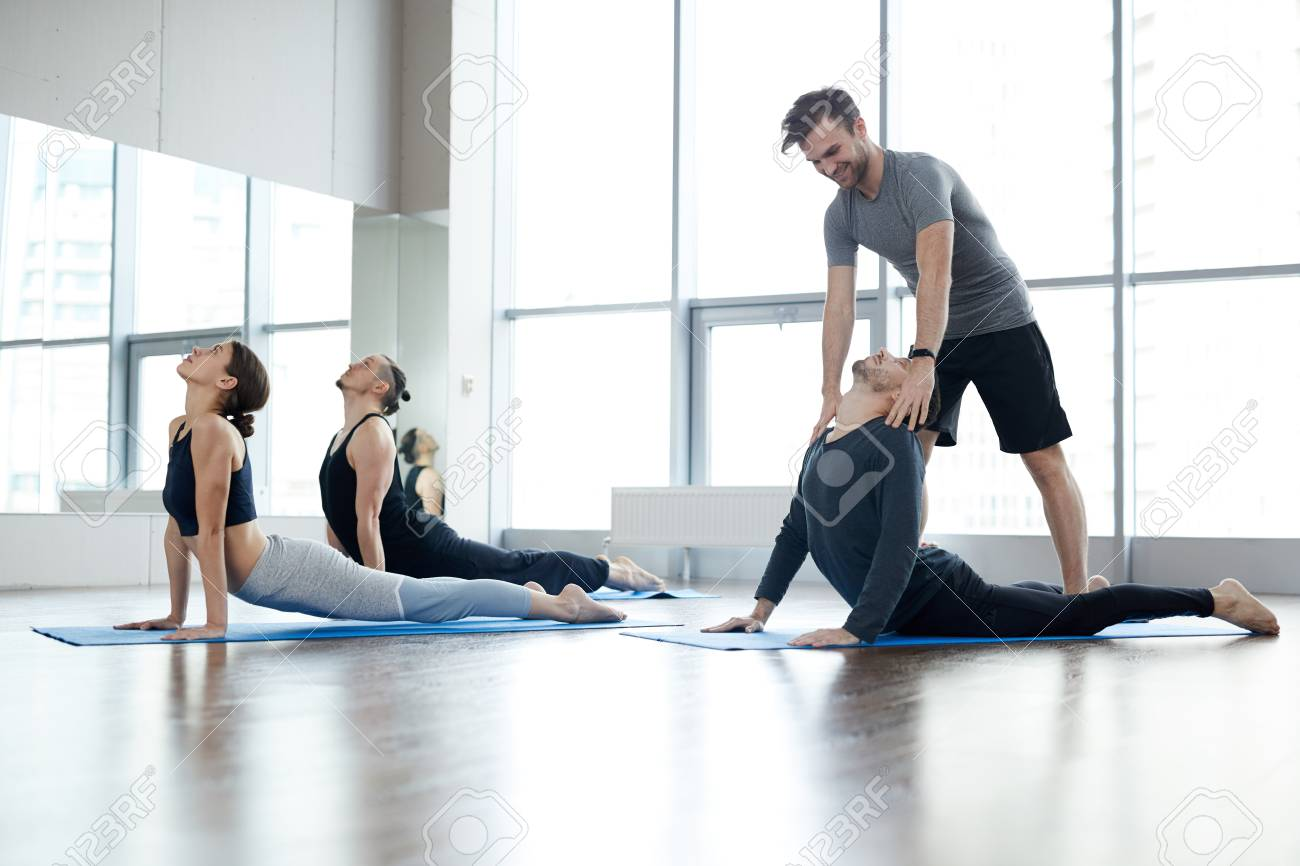 Young yoga instructor correcting cobra pose of students - 120888787