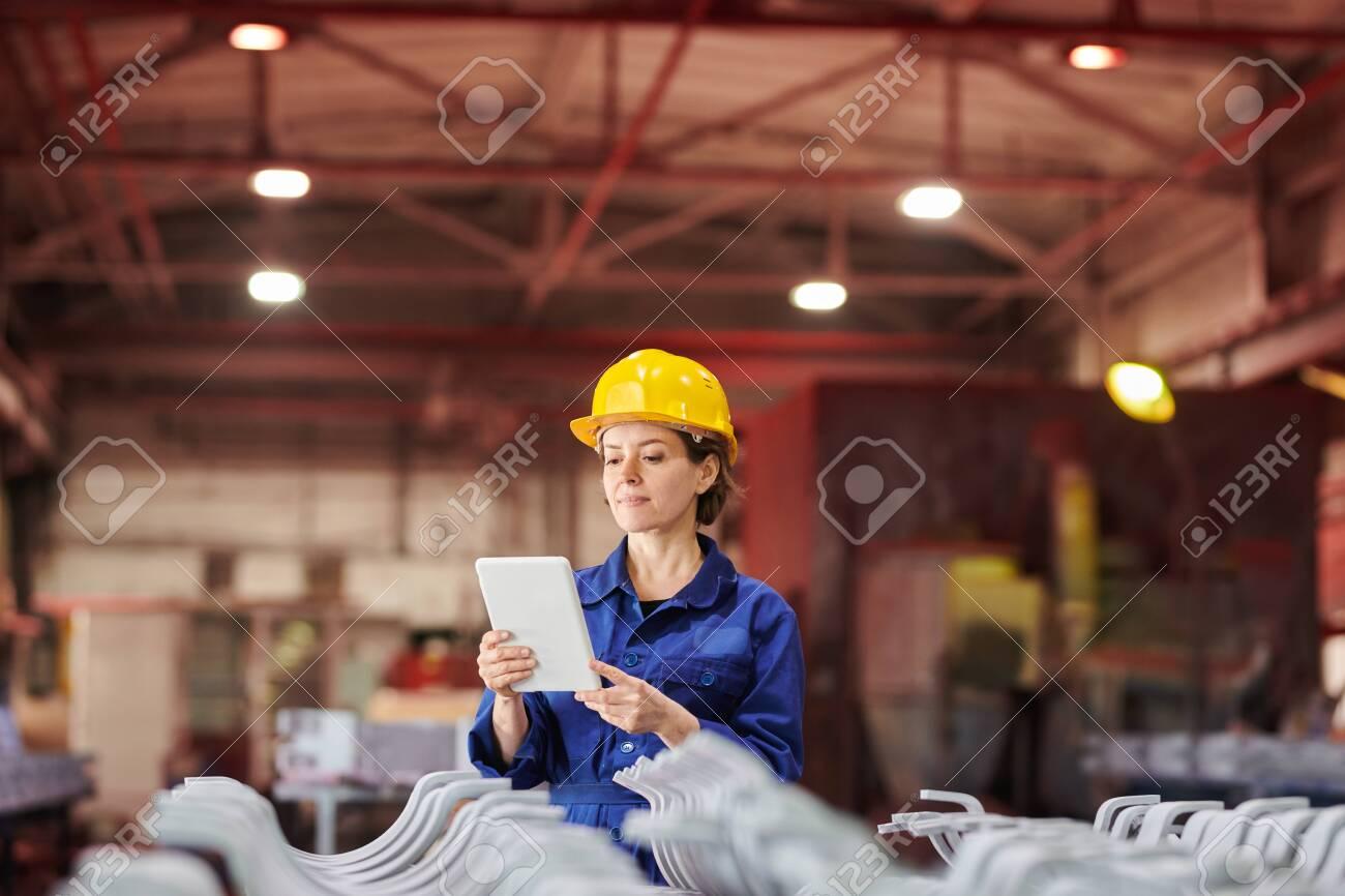 Smiling Woman Using Digital Tablet at Factory - 123189003