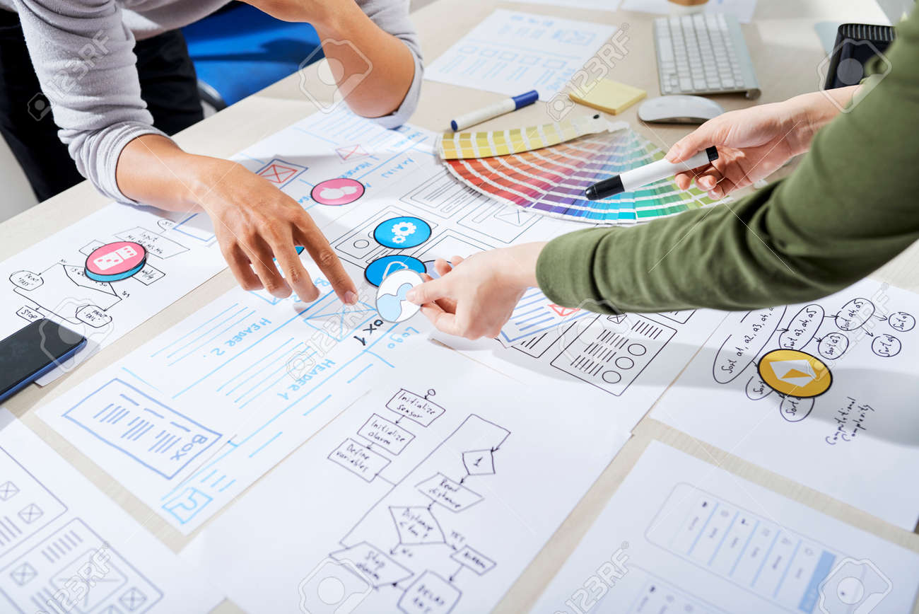 UX designers choosing icons for mobile application and discussing wireframe - 124773809