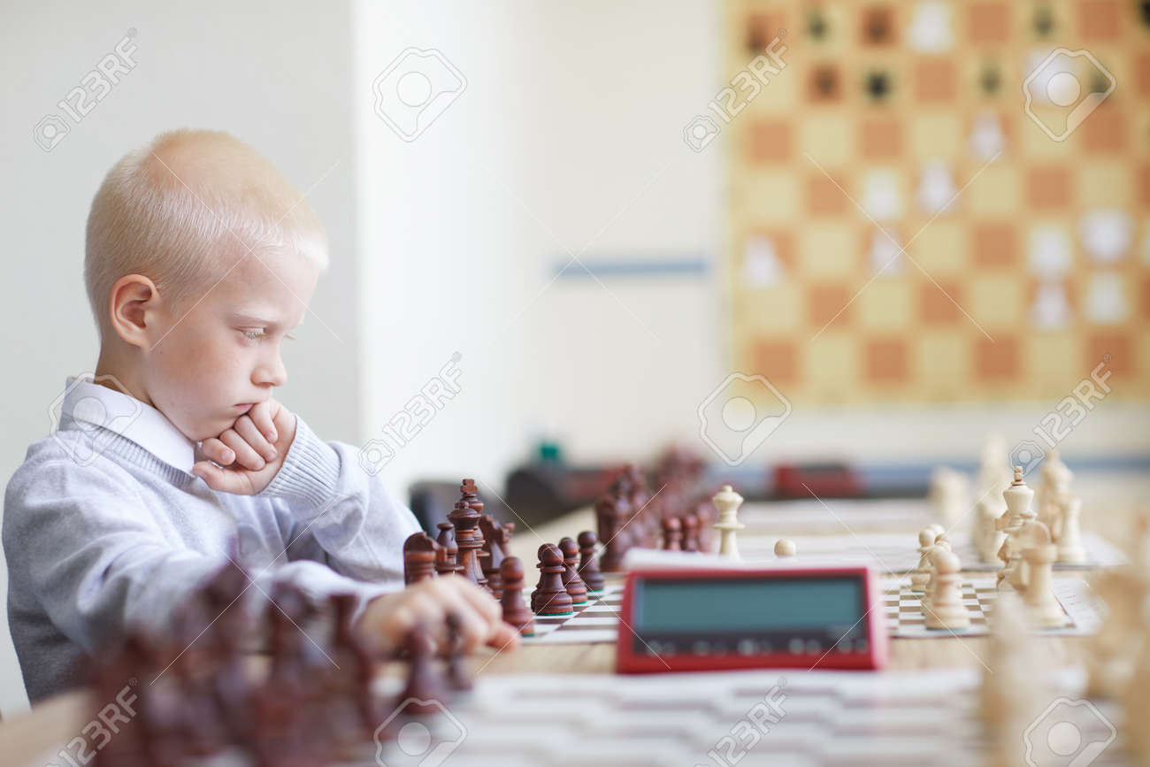 Serious schoolboy playing chess - 124775719
