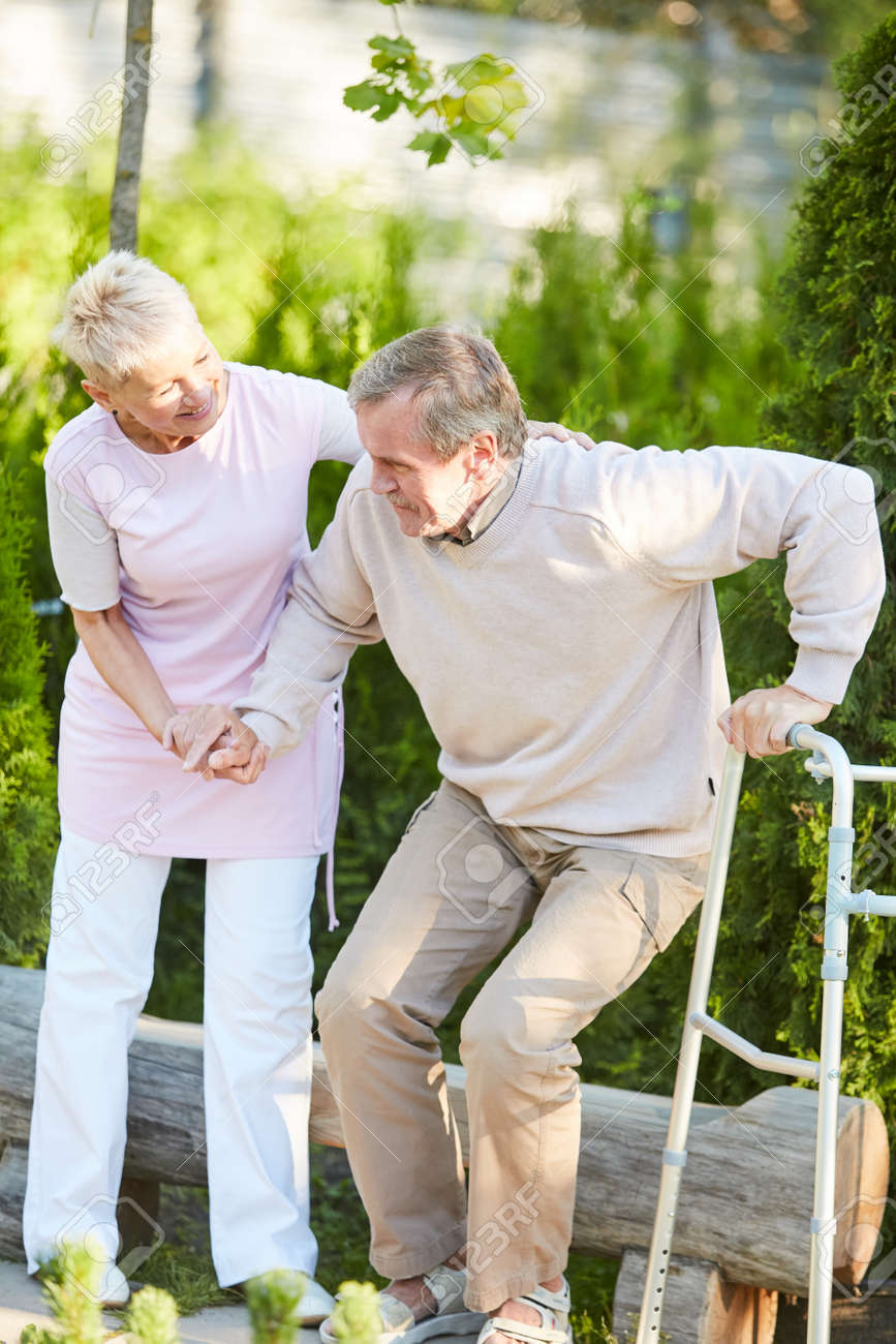 Full length portrait of caring nurse helping senior man get up from park bench in rehabilitation center, copy space - 127586374