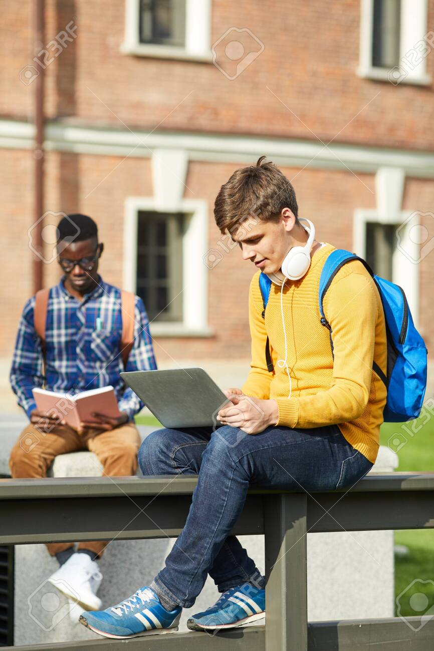 Full length portrait of contemporary college student using laptop sitting on table outdoors in campus, copy space - 128446461