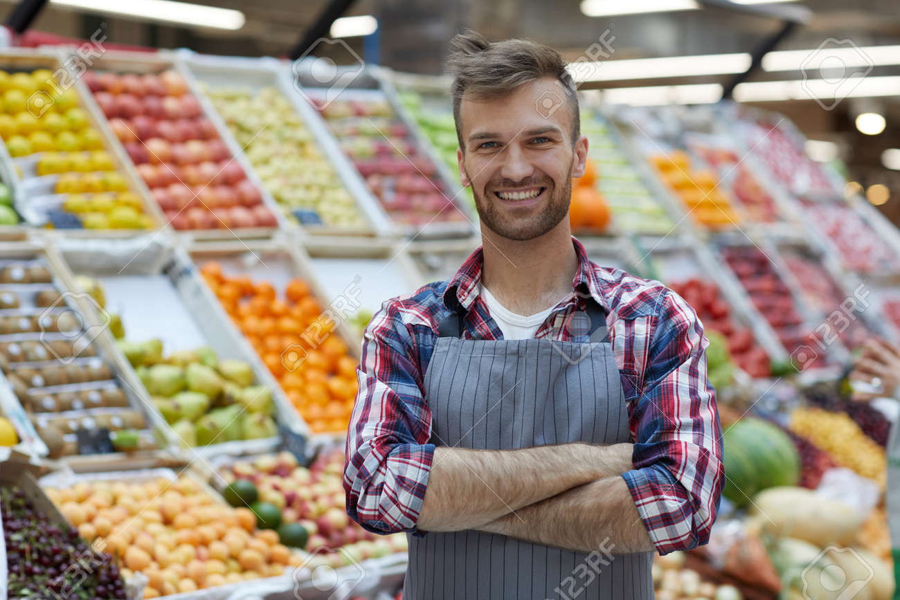 Waist up portrait of handsome young man working in supermarket and smiling at camera while posing by fruit stand, copy space - 128446655