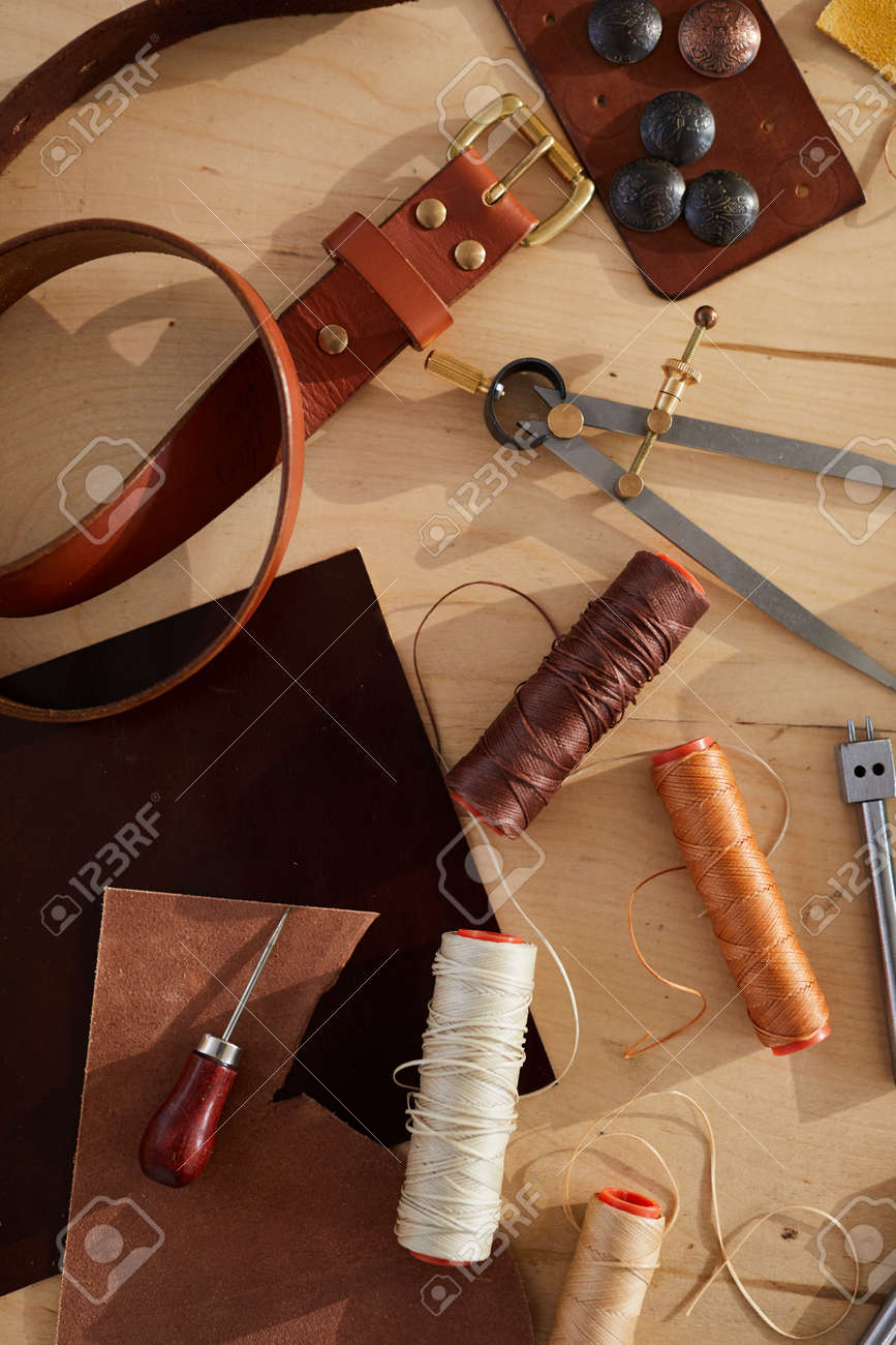 Above view background of tools and supplies scattered on wooden table in leatherworking shop, copy space - 128852410