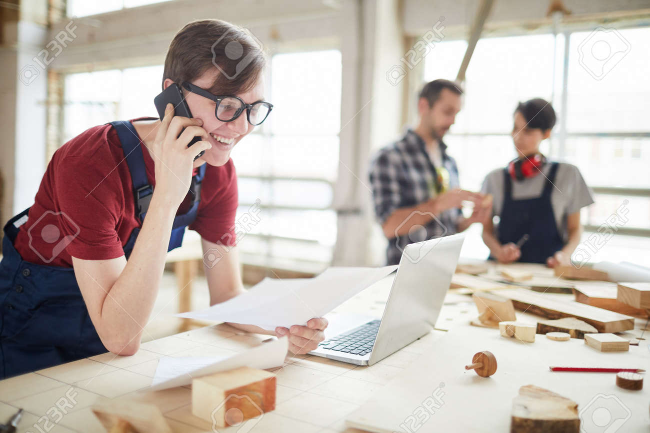 Portrait of modern carpenters working at woodworking factory, focus on smiling young man speaking by phone and using laptop in foreground, copy space - 129172637