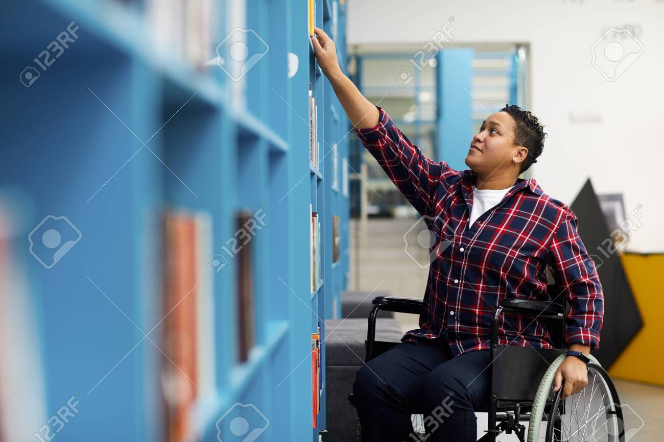 Portrait of disabled student in wheelchair choosing books while studying in college library, copy space - 132274294