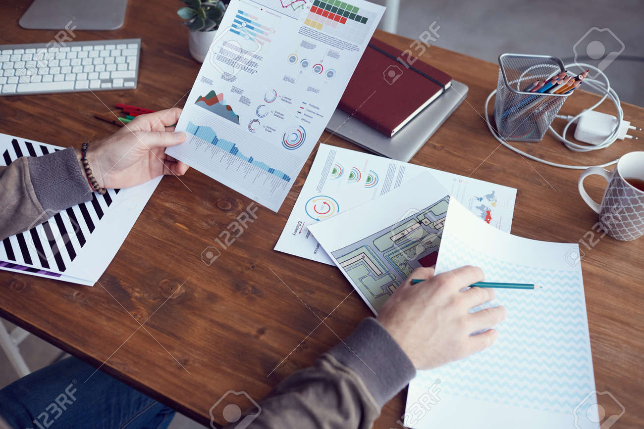 Closeup of unrecognizable modern businessman holding statistics report with colored data while working at wooden desk in office, copy space - 135269888