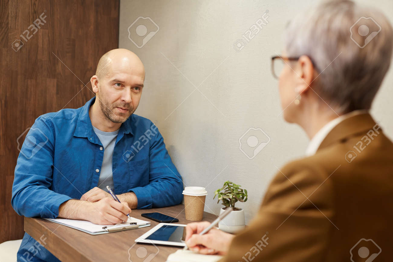 Portrait of mature bald man writing on clipboard while discussing contract with business manager during meeting at cafe table, copy space - 142918262