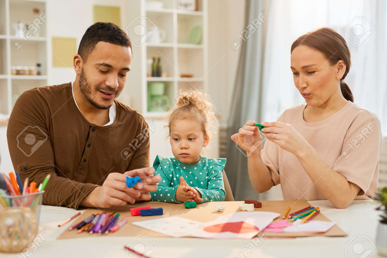 Loving parents spending with their little daughter sitting together at table making models using play dough - 146189538