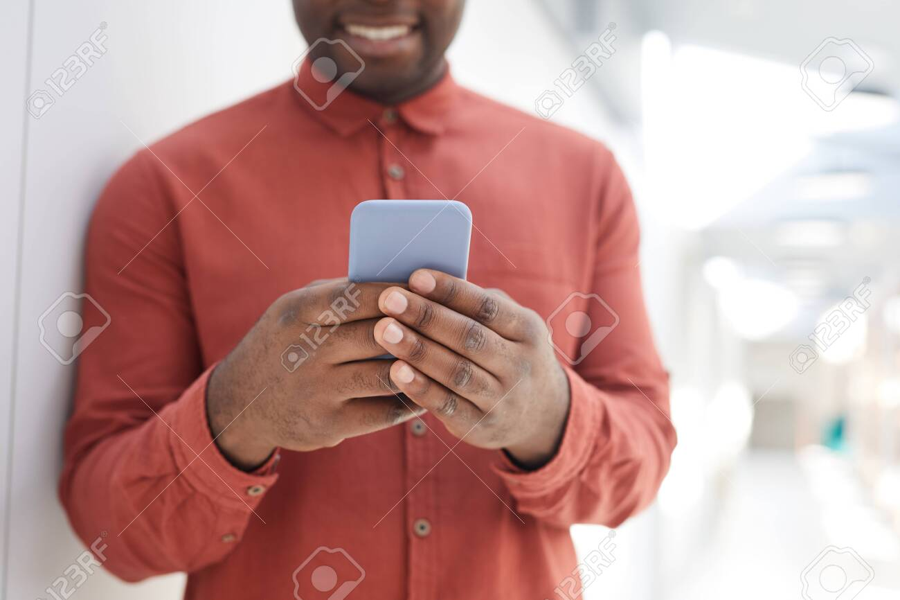 Mid section portrait of unrecognizable African-American man using smartphone while standing against while wall and smiling, focus on male hands holding phone, copy space - 148086956