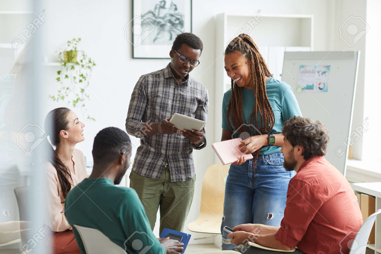 Multi-ethnic group of people sitting in circle while discussing business project in office, focus on smiling African-American woman talking to colleague standing up , copy space - 152790355