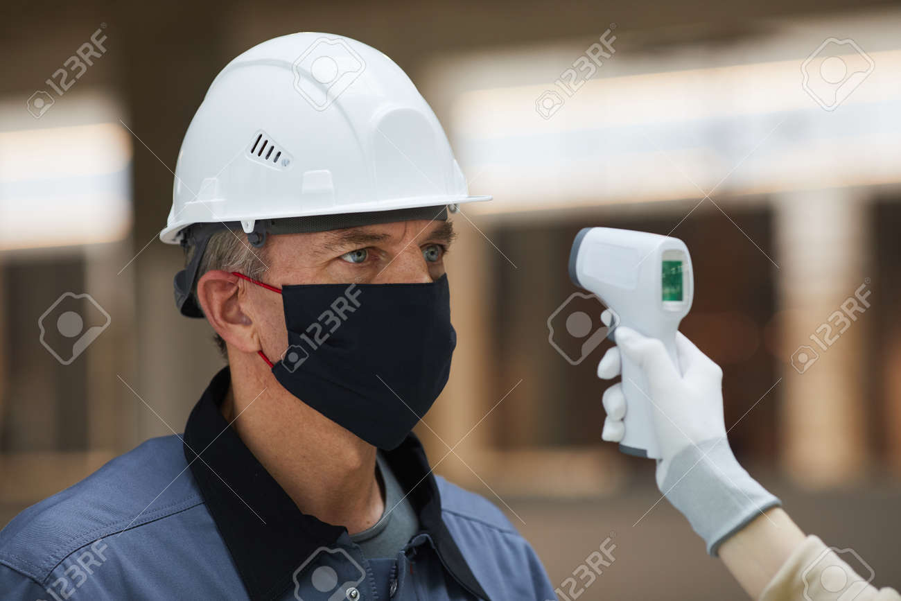 Portrait of mature worker wearing mask and waiting to measure temperature with contactless thermometer at construction site, corona virus safety - 157786809