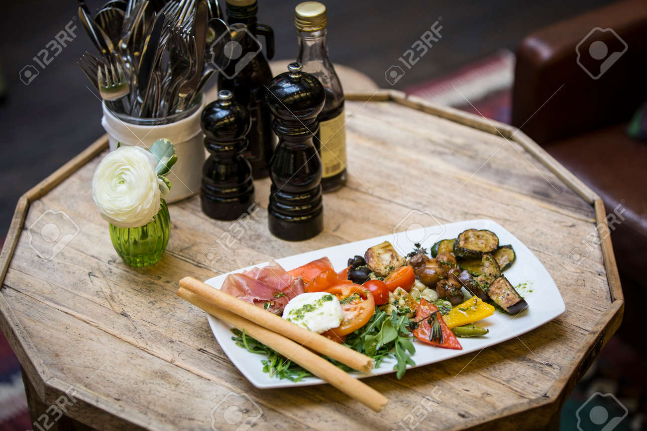 Appetizer Plate In Restaurant With Italian Antipasti And Table