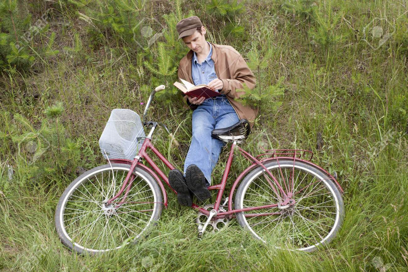 Man reads book, sitting on a mountain slope Stock Photo - 8525739