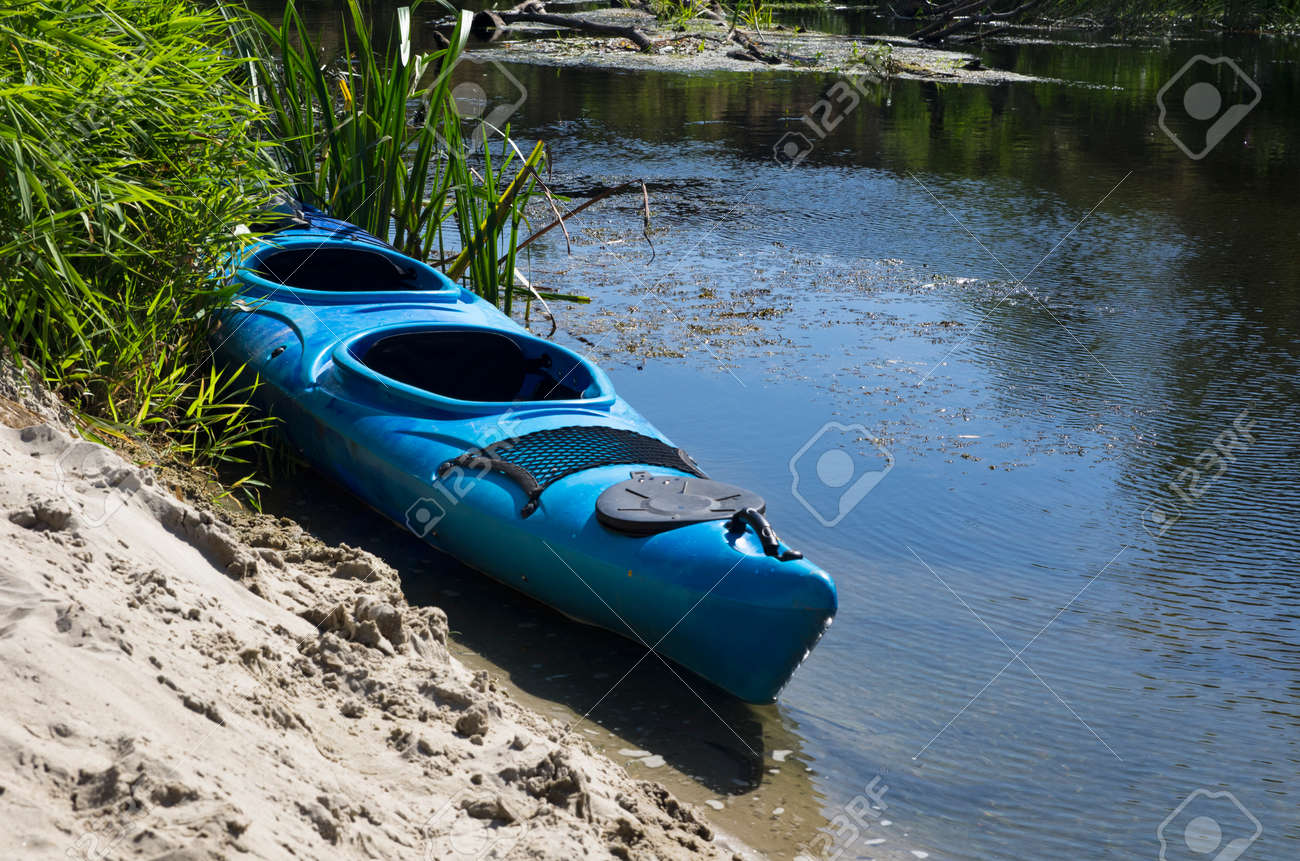Kayak on the sandy shore of a small river - 146541757