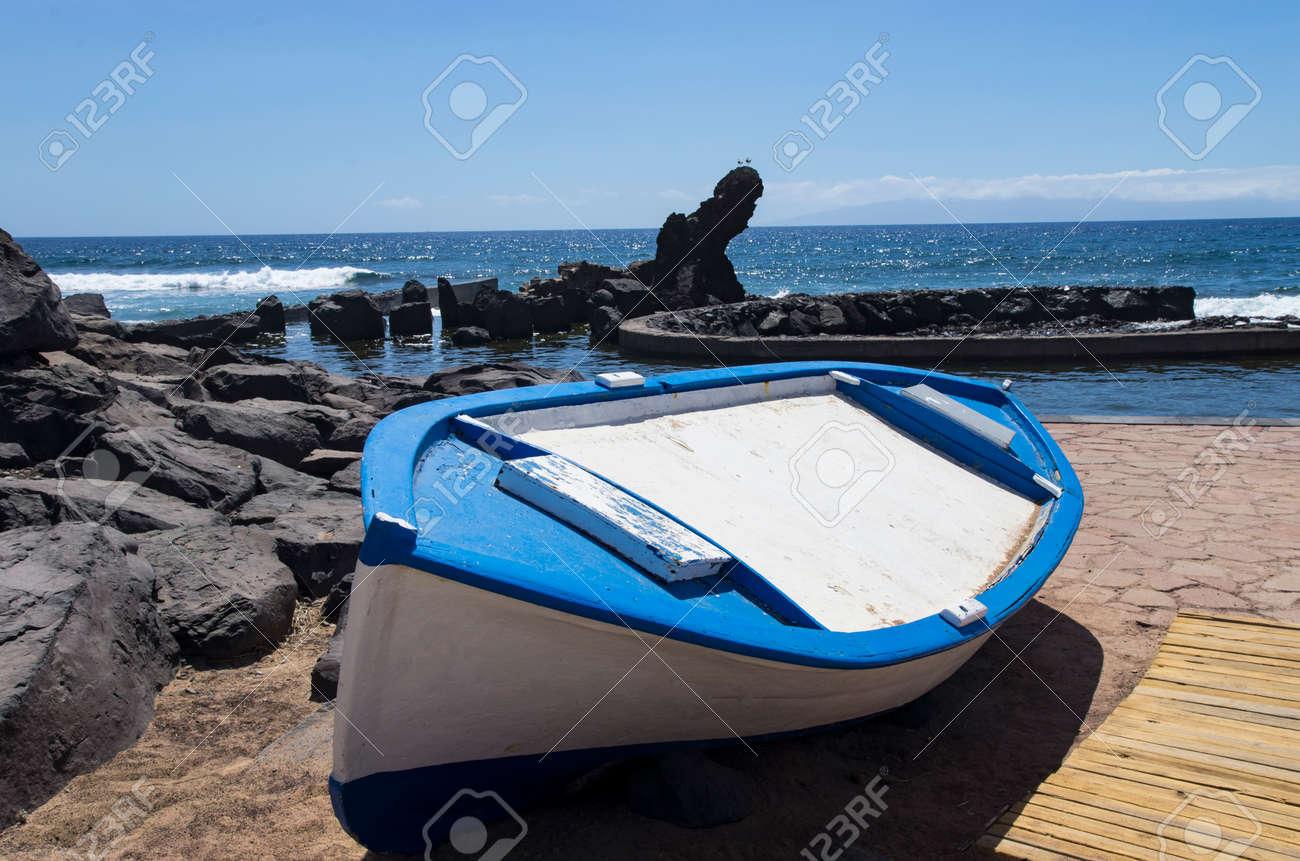Wooden boat on a stone seashore - 150500611