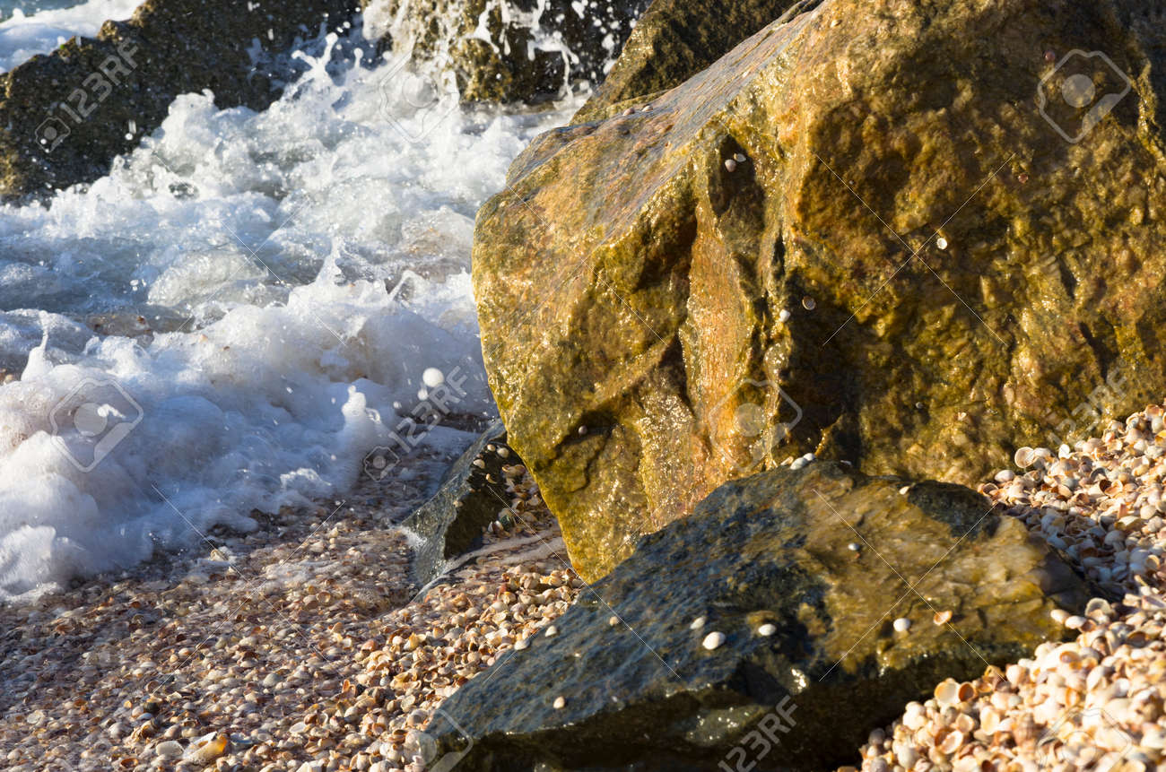Sea waves run into coastal stones - 158225424