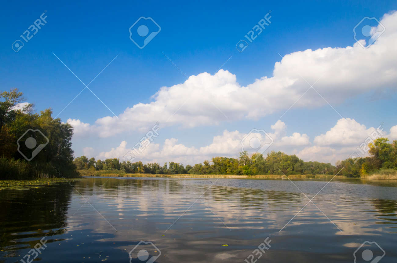 Landscape of an autumn river with vegetation along the banks - 158224335