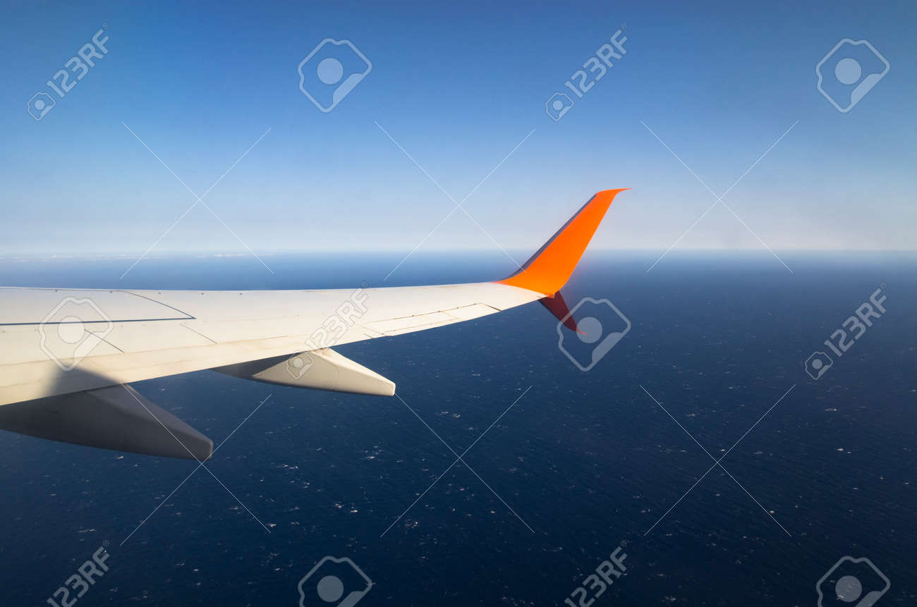 Airplane wing flying over the ocean - 158331025