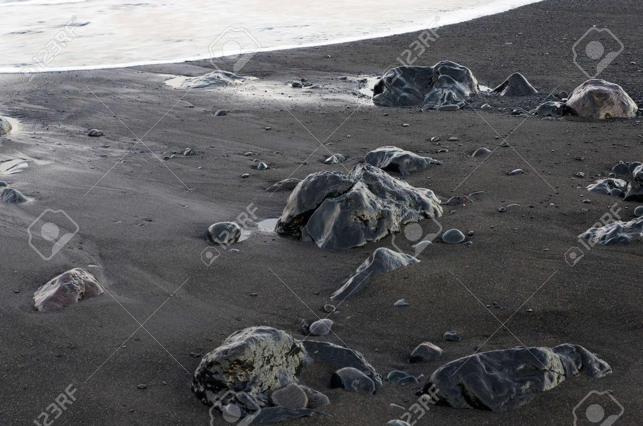 Black volcanic stones on black coastal sand - 159935611