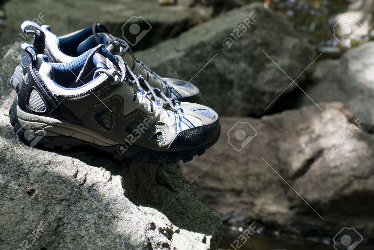 A pair of hiking shoes stand on granite stones - 159935637