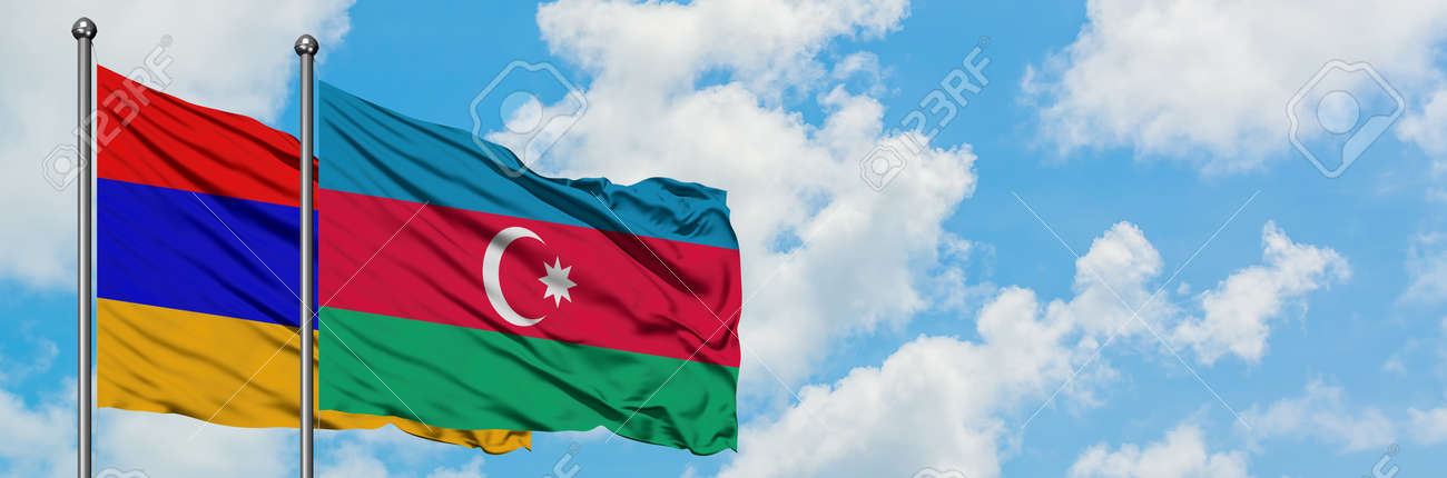 Armenia and Azerbaijan flag waving in the wind against white cloudy blue sky together. Diplomacy concept, international relations. - 122988982