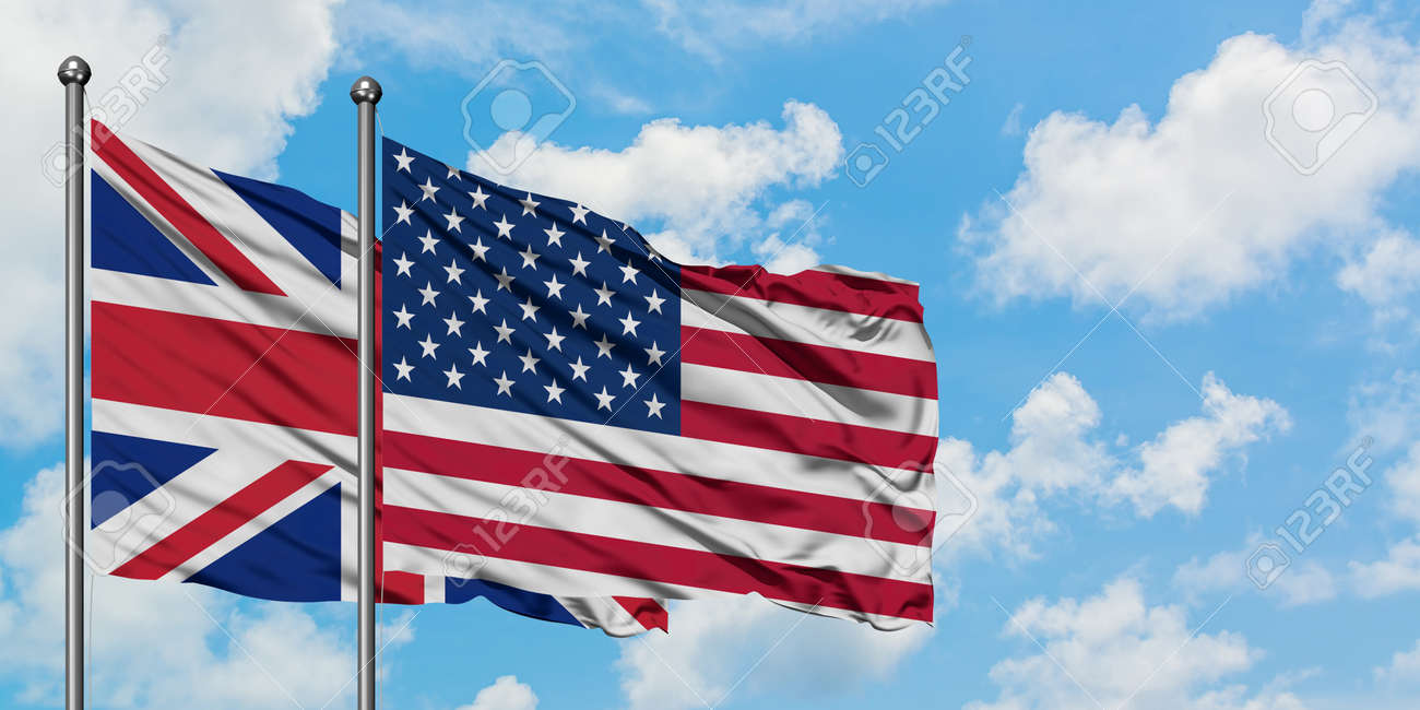 United Kingdom and United States flag waving in the wind against white cloudy blue sky together. Diplomacy concept, international relations. - 147532358