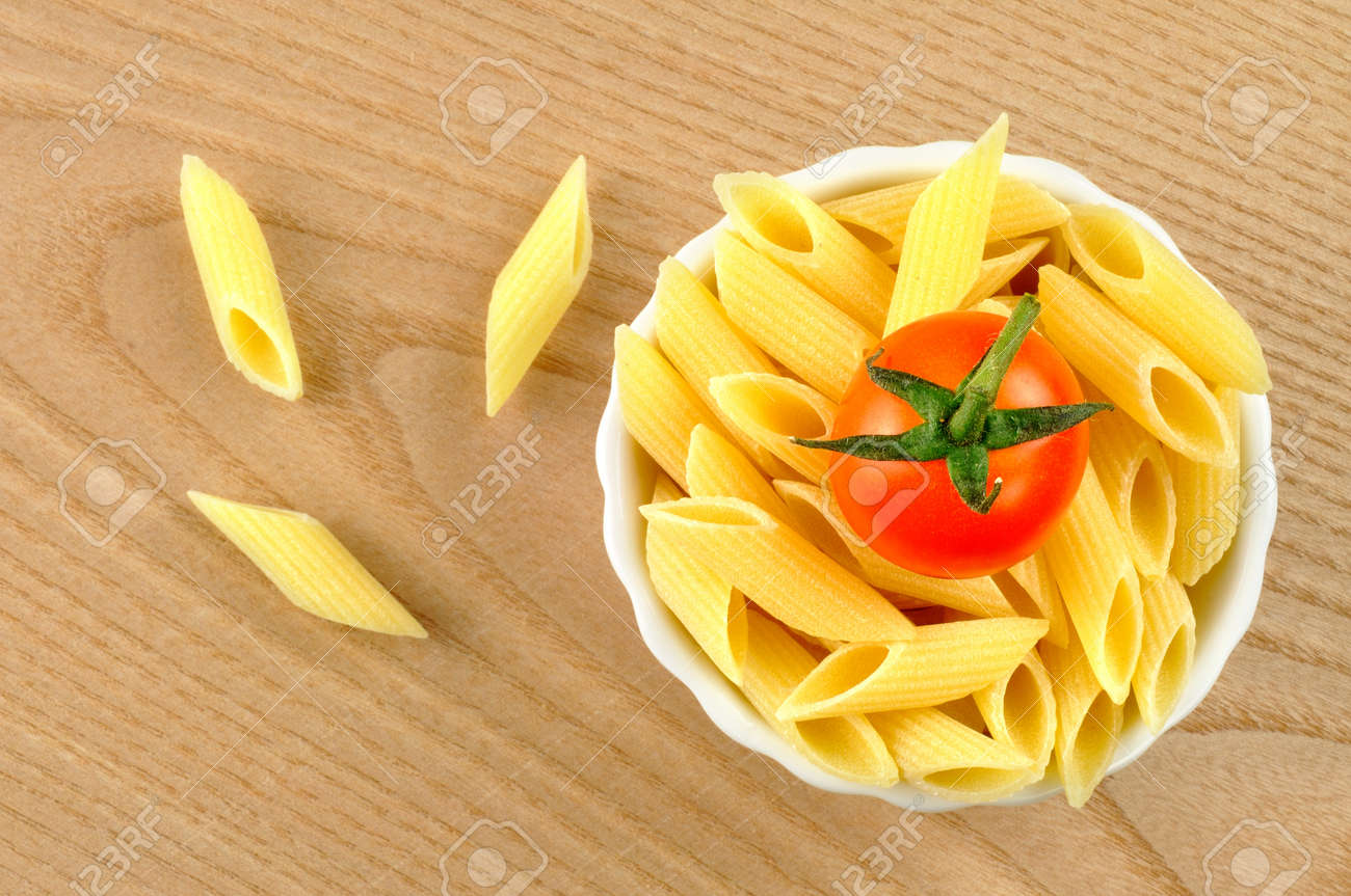 Several uncooked penne pasta and a cherry tomato in a small bowl Stock Photo - 15629788