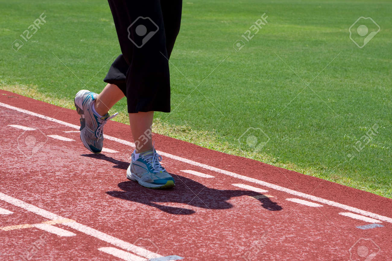 A Young Woman Running The Track In Black Pants And Tennis Shoes ...