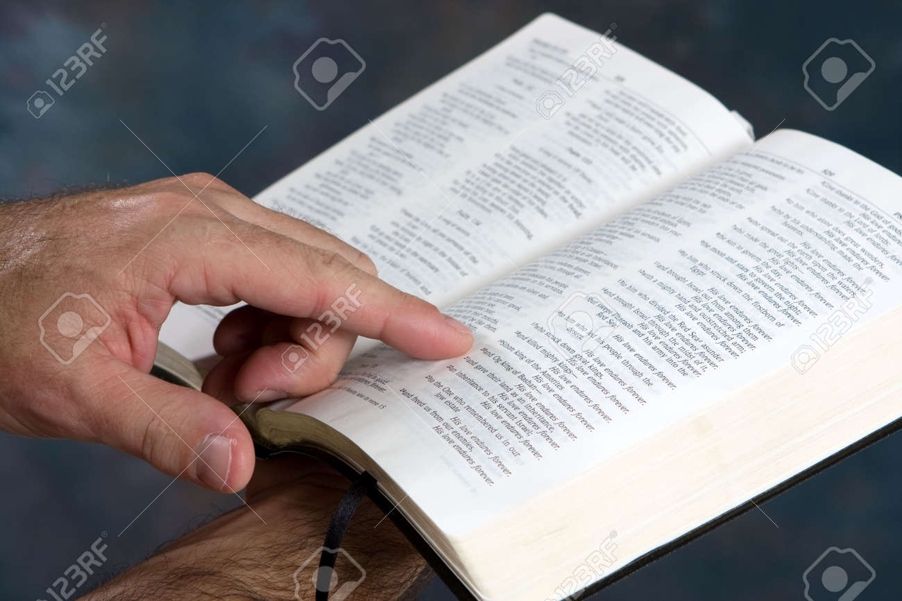 Man holds open bible and reads from scripture. Standard-Bild - 5645502