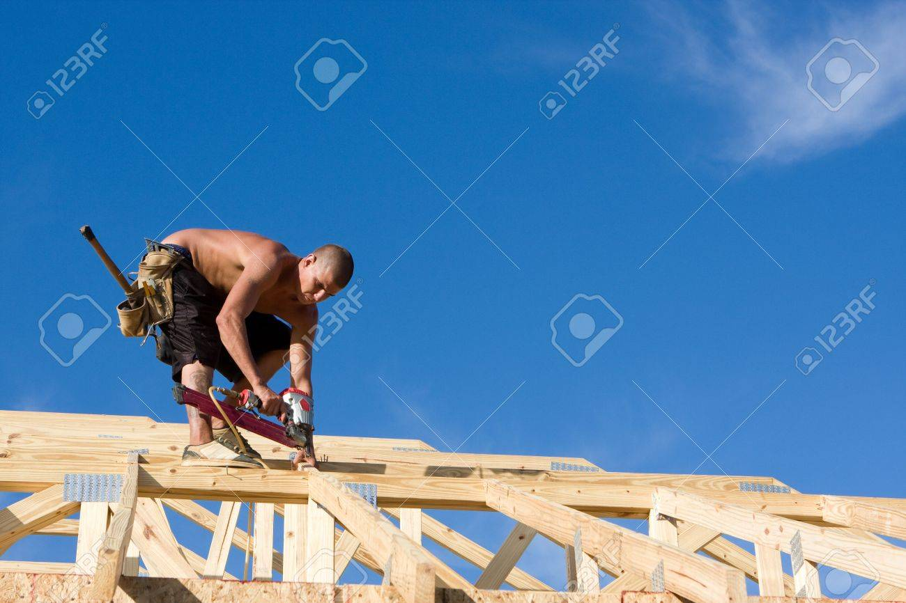 Carpenter uses a pneumatic nail gun to attach rafters and braces to a roof system on a new home under construction. Stock Photo - 5833599