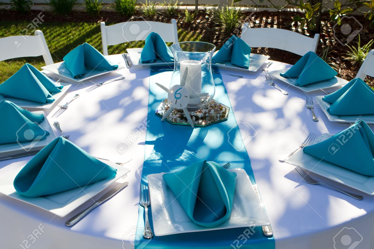 outdoor dinner table is setup with plate silverware and folded napkins for a wedding reception