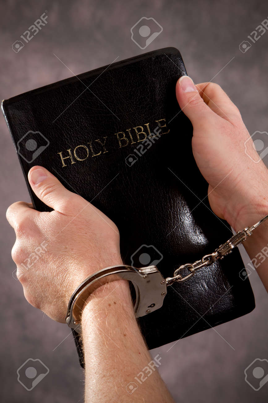 Handcuffed male hands hold a black Holy Bible. Stock Photo - 8678029