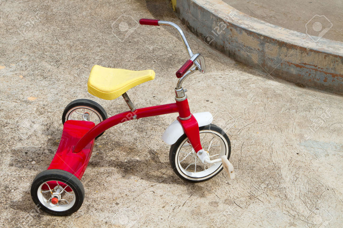 Abandoned red tricycle with a yellow seat sits on concrete pad. Stock Photo - 8776218