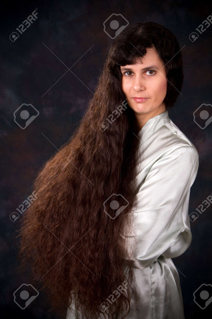Extremely long haired Middle Eastern woman in a light blue robe poses in front of a dark background. Stock Photo - 8960221