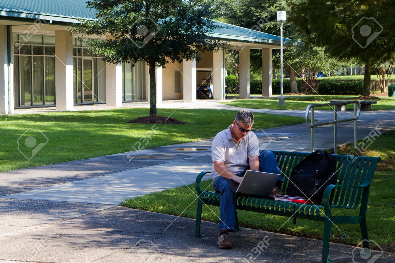 Middle aged student works on his laptop while sitting on a bench on a university campus outdoor area Stock Photo - 15402799
